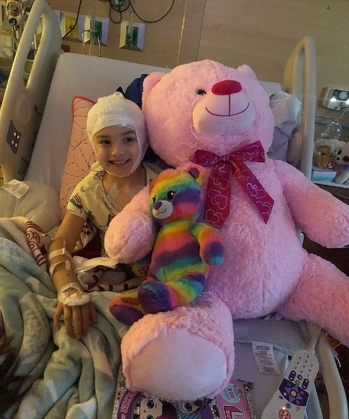 Liza sitting happy with a big teddy bear to make her feel better.