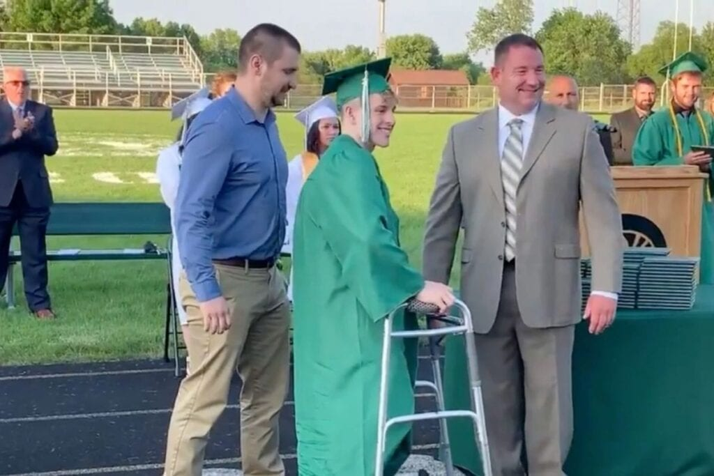 High school senior paralyzed during football game gets standing ovation as he walks at graduation