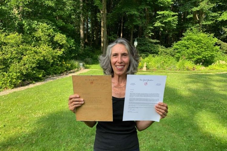 Gwen Goldman holding the two letters from former and current Yankees GMs.