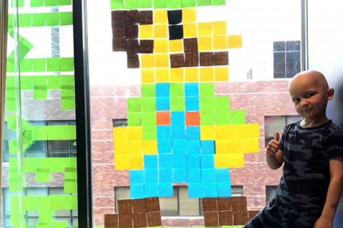Boy undergoing cancer treatment makes new friends with hospital staff across the street using Post-it notes.