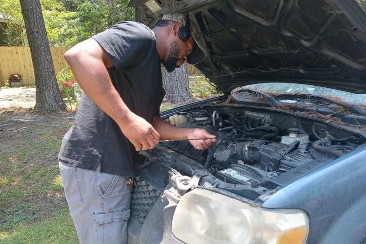 Eliot Middleton fixing a donated car to give to someone in need.