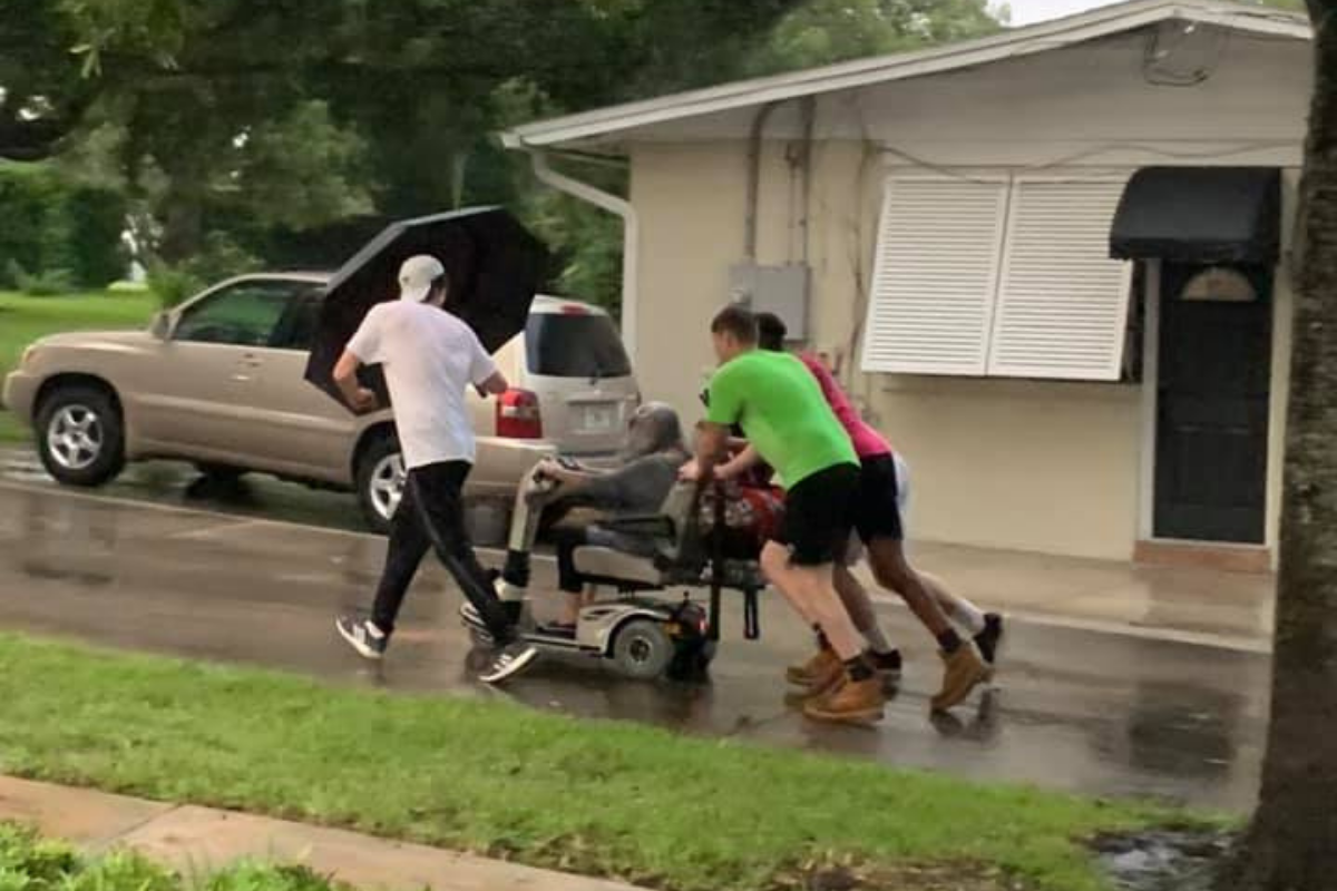 Four young men push elderly woman home after her electric scooter broke down in the pouring rain.